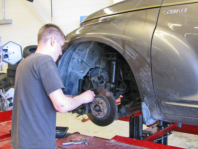 student working on brakes