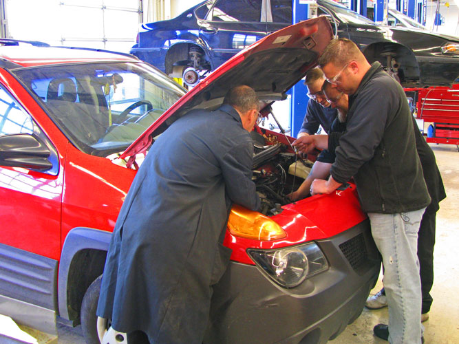 Students and instructor under the hood of a car
