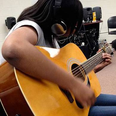 student playing a guitar