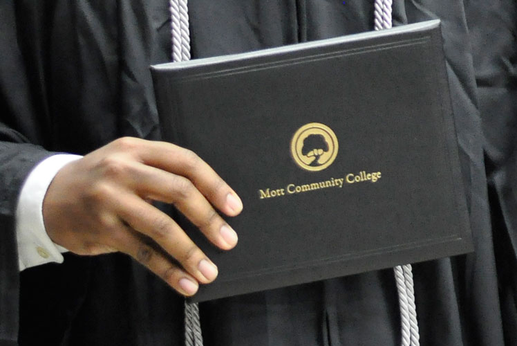 Student hand in graduation gown holding Mott Community College diploma