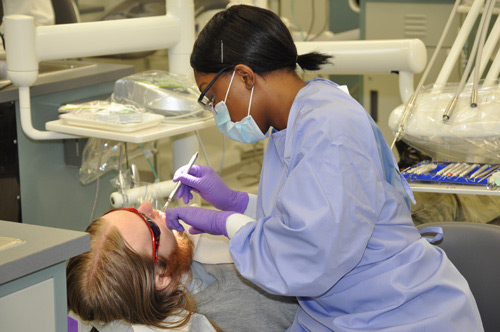 Dental Hygiene student cleaning a fellow students teeth