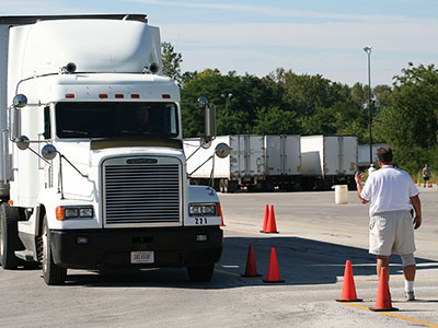 image off semi-truck navigating a road course with orange cones with a man off to the side giving directional hand signals
