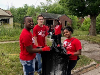 Group of Teens in SYI program doing outdoor clean up activity
